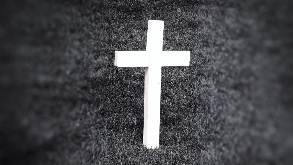 black and white photo of white cross in grass