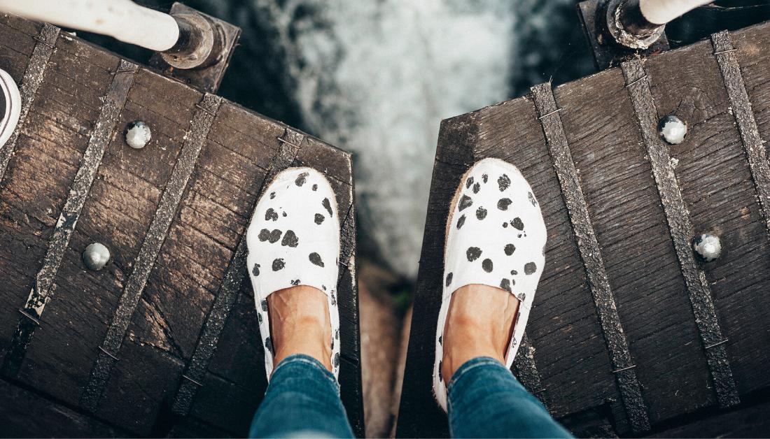 feet on bridge over water
