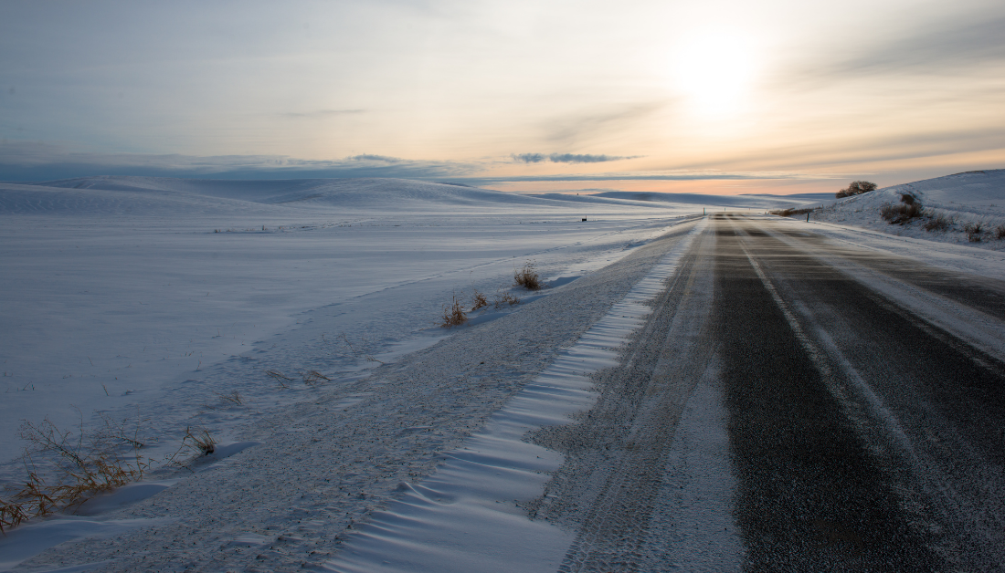 snowy landscape with road leading towards glimmer of sun