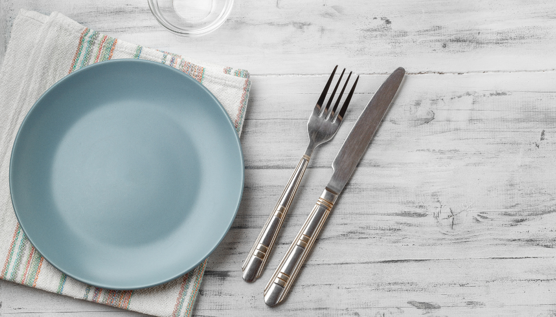 image is a plank table set with a blue plate, napkin, and fork and knife