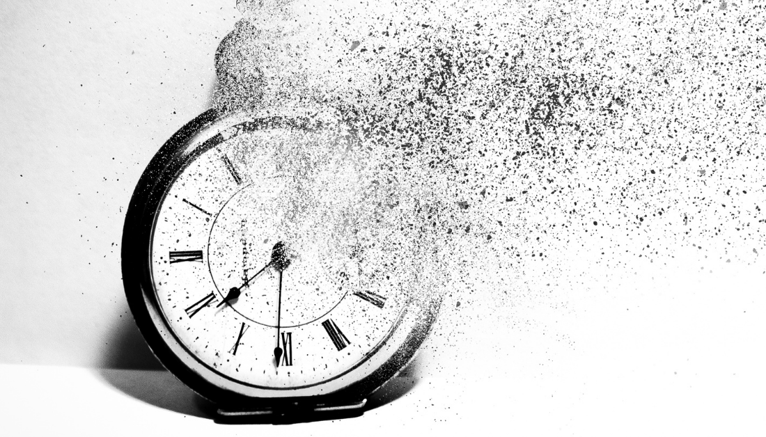 black and white image of an old fashioned alarm clock with a part of it disintegrating