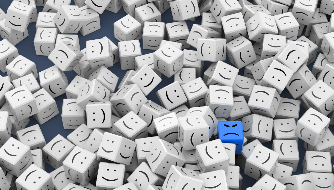 picture of white dice with happy faces and one blue dice with a grumpy face