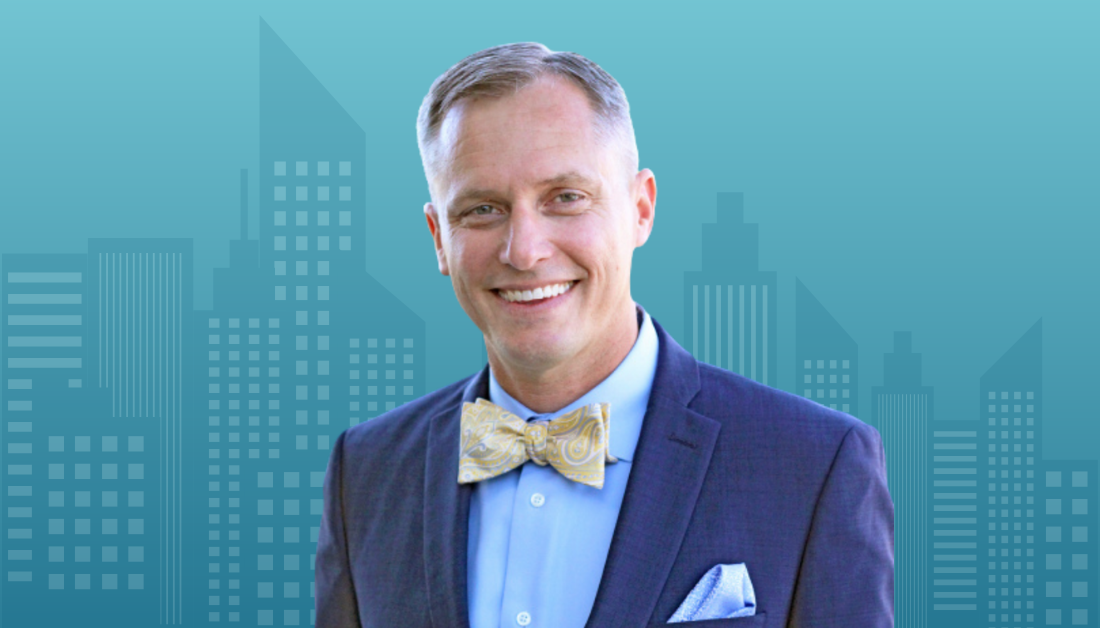 picture of David Swanson on a gradient blue background with cityscape