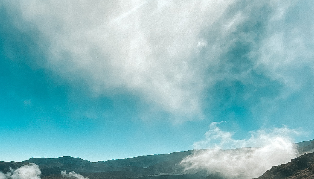 picture of the tops of mountains with wispy clouds above and below