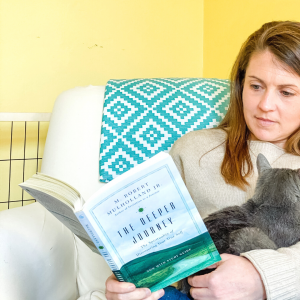 Amy Julia sitting in a white chair reading a book and holding a gray kitty