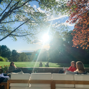 picture of women sitting on a deck with sunlight filtering through trees illustrating healing from covid-19 in community