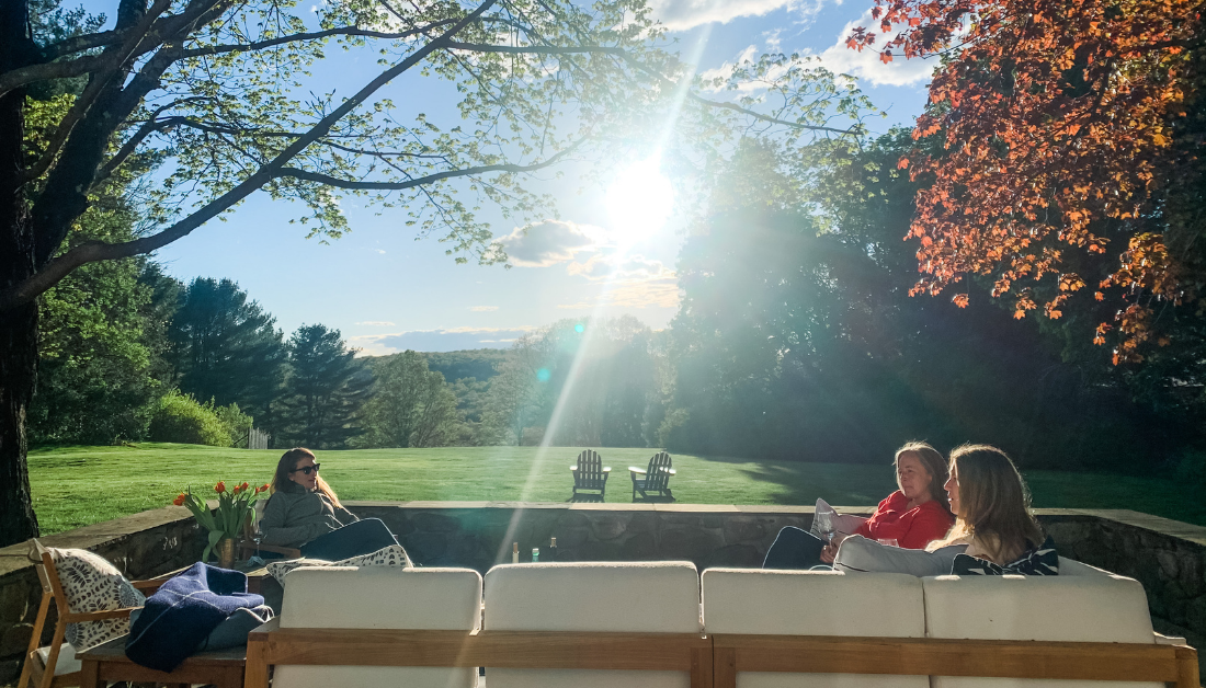 picture of women sitting on a deck with sunlight filtering through trees