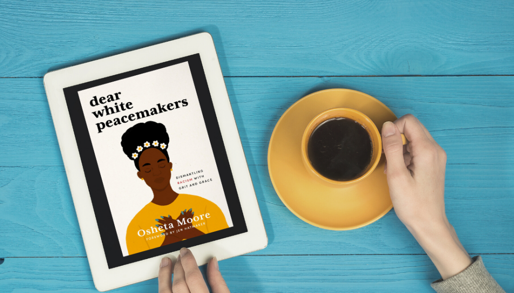 picture of a blue table and a pair of hands holding an ipad with a picture of Dear White Peacemakers and holding a cup of coffee