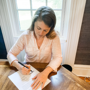 introduce myself picture of Amy Julia siting at a wooden table looking down signing a piece of paper with a window behind her
