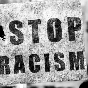 black and white photo of a sign that says Stop Racism