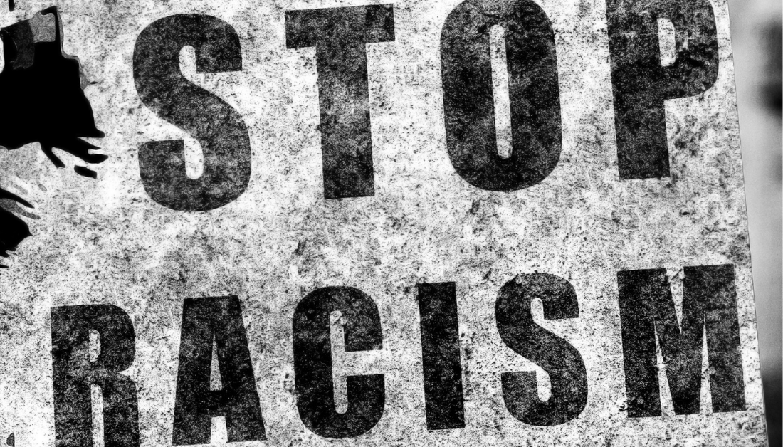 black and white anti-racism photo of a sign that says Stop Racism