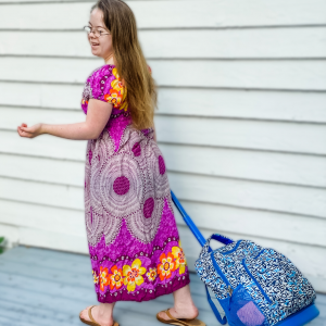 Penny, who has Down syndrome, walking away from the camera pulling her back pack on her way to high school