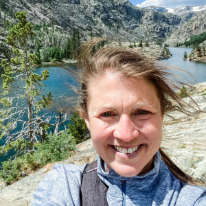 picture of Amy Julia smiling with welcome at the camera with a lake and mountains behind her