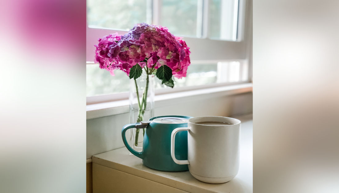 picture of pink flowers in a vase on a counter next to an open window and two mugs sitting next to the vase; one mug is greenish-blue and upside down and one mug is white and filled to the brim with tea