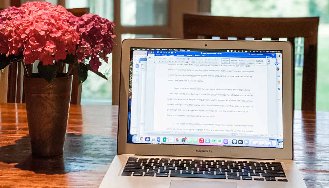 picture of a laptop on a wooden table with a vase of flowers next to the laptop and windows in the background