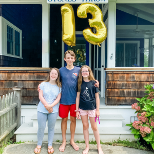 William standing in-between Penny and Marilee with his arms around them. All three are looking at the camera and smiling. There is a gold 13 balloon hanging from the porch in the background