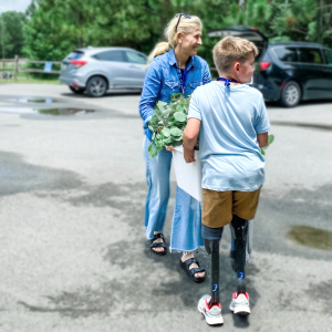 a woman and a young boy with prosthetic legs carrying plants together