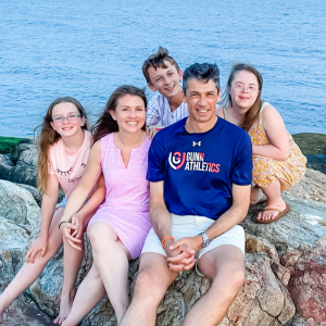 Amy Julia's family sitting on rocks with a water behind them
