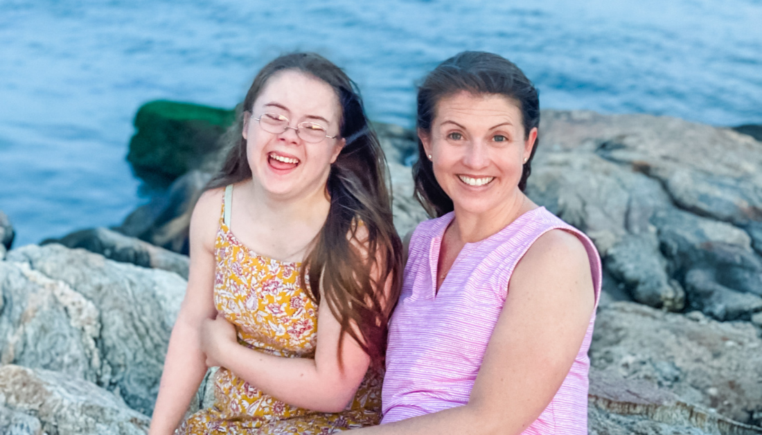 Penny and Amy Julia sitting on rocks next the ocean. Penny is laughing and Amy Julia is smiling at the camera