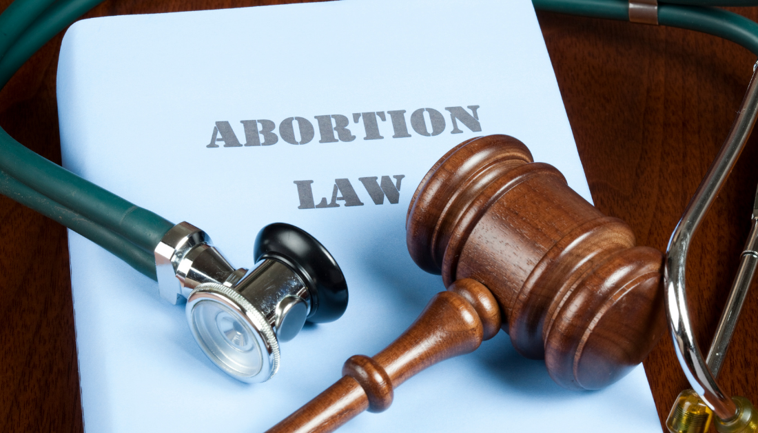 a blue book that says Abortion Law, with a stethoscope wrapped around it and a gavel on top of it