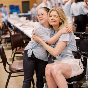 Penny, who has Down syndrome, and Katherine Wolf, who is sitting in a wheelchair, giving each other a hug at Hope Heals Camp
