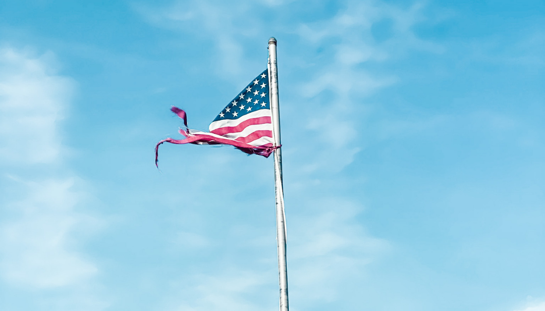 tattered flag blowing in the wind with blue sky and clouds in the background