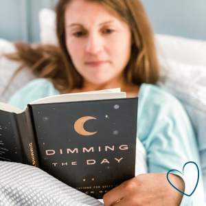 Amy Julia reclining in bed reading Dimming the Day