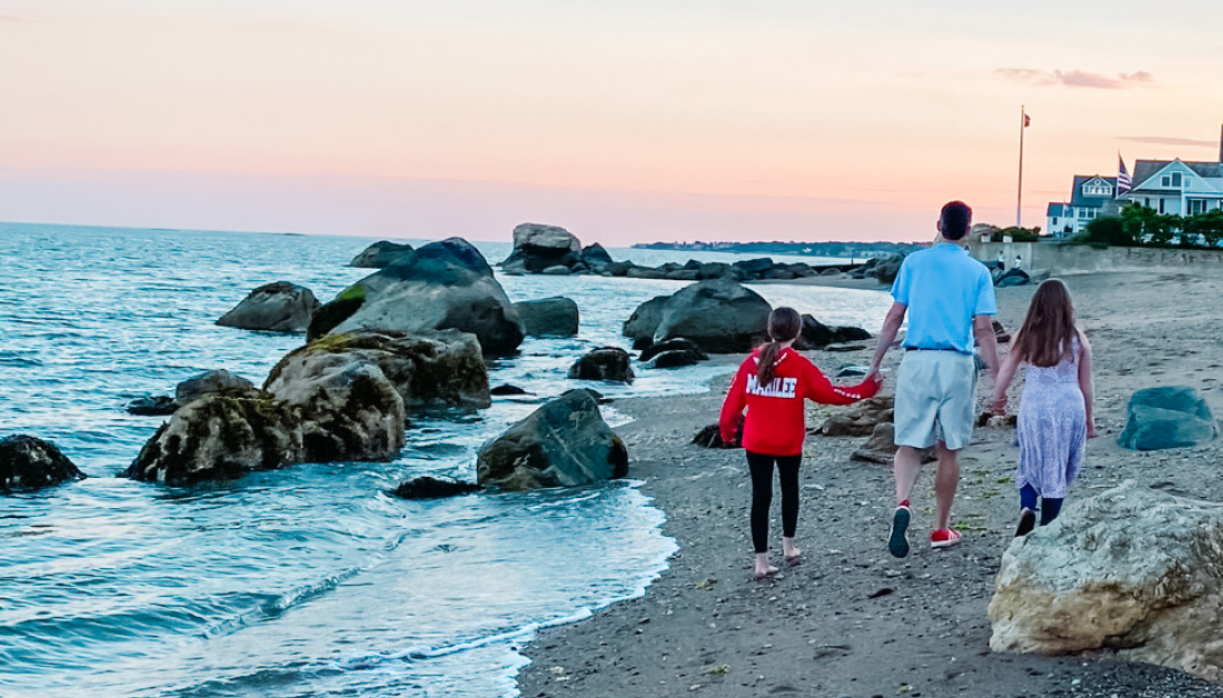 a grown up and two children walking away from the camera along the beach with water rippling around rocks to their left